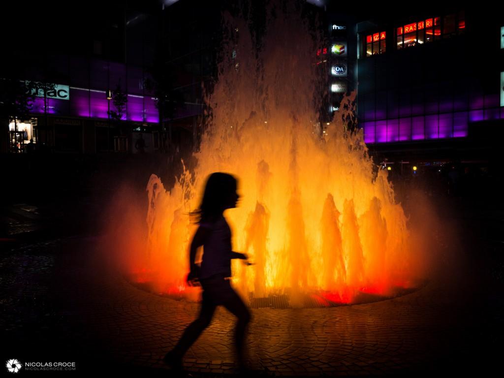 Un enfant joue devant la fontaine de la place de Jaude, qui simule un volcan en éruption
